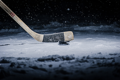 hockey stick and puck on ice rink